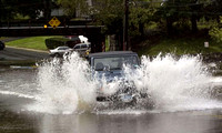 A vehicle successfully attempts to drive through the rushing water along West Street in Danbury