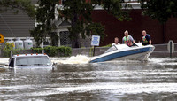 A motorboat passes a submerged pickup truck on Main Street in Washingtonville, N.Y