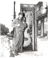 Standing beside a mud cakes, useless telephone booth, victim of the flood, Cpl. Joseph Ferraro overcomes communication breakdown by using walkie-talkie to relay message from River St. and South Washin