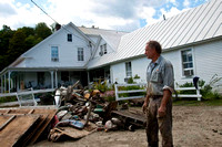 George Schenk, owner of American Flatbread and the Inn at Lareau Farm in Waitsfield, looks over a pile of flood ravaged goods removed from the inn and restaurant
